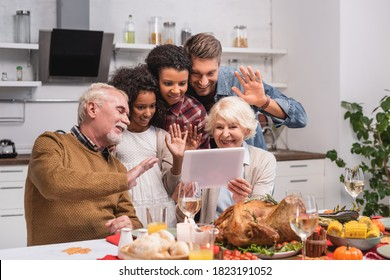 Selective focus of multicultural family waving at digital tablet during video call and thanksgiving celebration