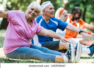selective focus of multicultural retired men and women in sportswear sitting on fitness mats