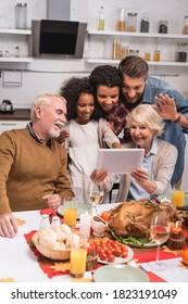 感謝祭の間、トルコの近くのデジタルタブレットでビデオチャットを行う多民族家族の限定フォーカス