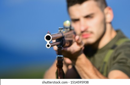 Selective focus. muscular man hold weapon. purpose and success. polygon combat exercises. military style. army forces. sniper reach target. man ready to fire. hunter hobby. aimed gun barrel.