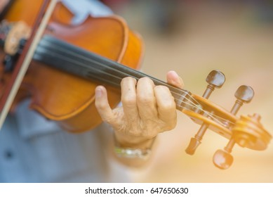 Selective Focus Musician play violin on dark background, close up