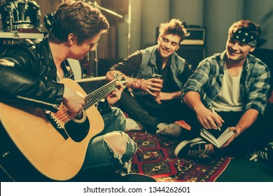 selective focus of musician playing acoustic guitar near happy friends sitting with crossed legs