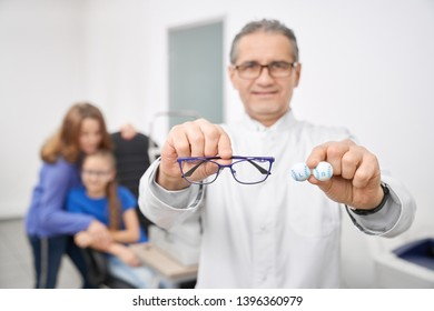Selective focus of new glasses and qualitative lens for better vision in optical store. Male oculist looking at camera while offering eyewear for clients at background. Concept of sight correction.