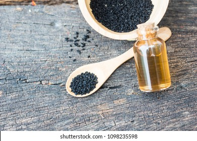 Selective focus Nigella sativa (Black cumin) on wooden spoon and essential oil. Real oil from nigella looks like dark honey. Herbal medicine.