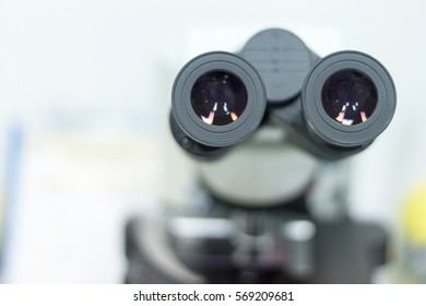 Selective focus of ocular eyepiece lenses and tube of binocular microscope for lab technician in laboratory research in hospital or university with white copyspace.Science Education Day