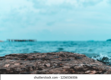 Selective focus od black stone texture for put product to show with beach in background.