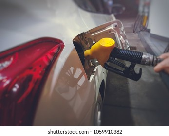 Selective focus on attendant hand controlls yellow fuel nozzle pumping the Gasoline to gas car tank.