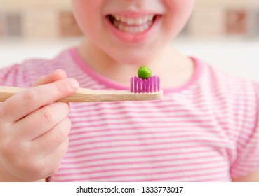 Selective focus on bamboo tooth brush with green pea on it and smiling blurred anonymous girl on background. Children should use the size of a pea amount fluoride toothpaste on brush concept.