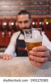 Selective focus on beer glass in the hands of bartender