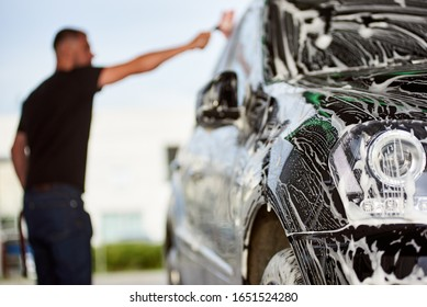 Selective focus on the black car with soap. On the blurred background man is washing his car with a brush and soap outdoors, side view, close-up