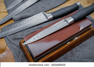 Selective focus on the blade of a steel kitchen knife lying on a water whetstone. The process of sharpening a knife blade to razor sharpness. On a blade transparent drops of water.