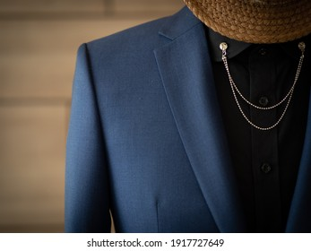 Selective focus on blue jacket blazer suit with black shirt and vintage silver collar pin detail close up