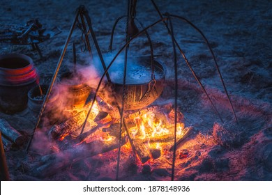 Selective focus on boiling cauldron with mysterious decoction on campfire at night witch sabbath. Kupala Night, called in Poland Noc Kupaly, Slavic holiday celebrated on the shortest night of the year - Shutterstock ID 1878148936