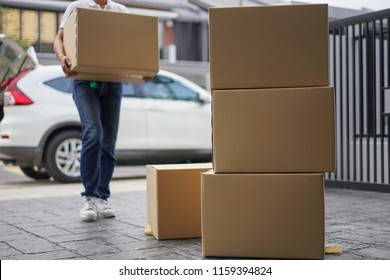 Selective focus on box while young men unloading box