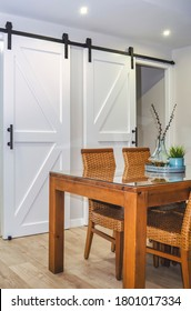 Selective focus on a bright dining room with a wooden table and rattan chairs. White sliding barn doors in the background.