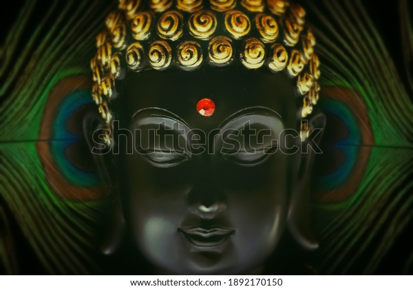 selective focus on buddha face with peacock feather behind isolated over black background