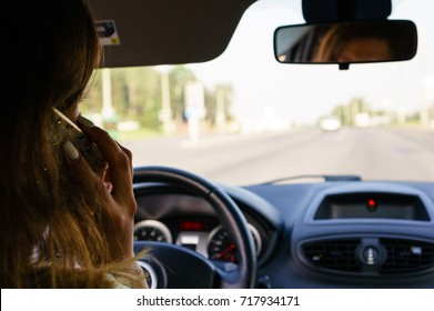 Selective focus on businesswoman talking on the smart phone while driving a car, rear view