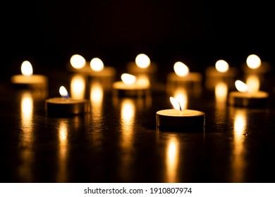 selective focus on candles on reflecting surface and black background