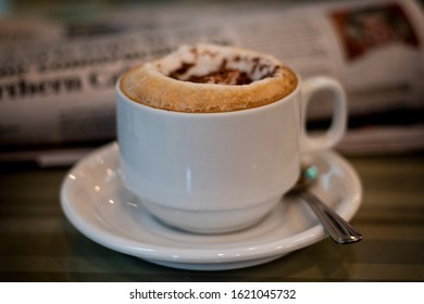 Selective focus on cappuccino on table at a cafe, with a blurred newspaper in the background, side view- coffee time the old way