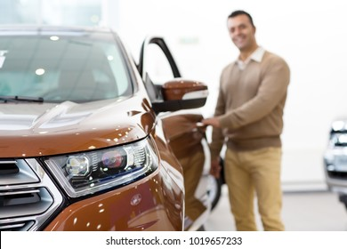 Selective focus on a car light male customer openign the door of an auto on the background copyspace driving travelling tourism comfoerl leasing rental retail sales discount offer SUV.
