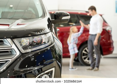 Selective focus on a car little girl high fiving her father on the background family buying new automobile consumerism lifestyle travel bonding happiness vehicle rental service concept copyspace