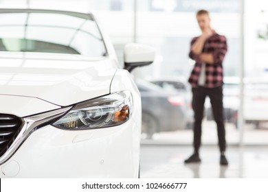 Selective focus on a car male customer choosing a new auto to buy at the dealership running his chin thoughtfully copyspace thinking consumerism buying service rental purchasing luxury lifestyle.