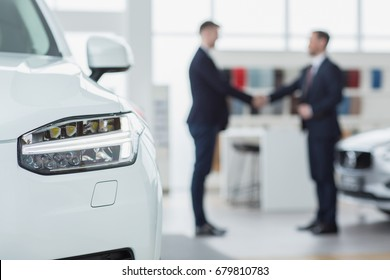Selective focus on a car professional salesman shaking hands with his client after selling him a new automobile on the background men handshake contract deal buying agreement communication copyspace