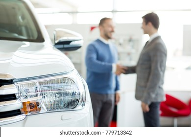 Selective focus on a car professional salesman and his customer shaking hands on the background copyspace lifestyle retail selling buying agreement leasing professionalism helpful service