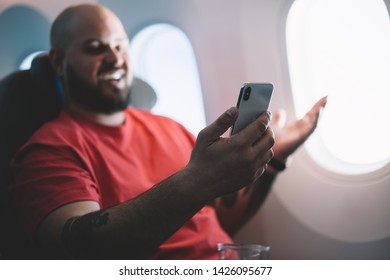 Selective focus on cellular which young smiling man holding in hands. Happy male flight passenger connecting to wireless internet on board sitting next to aircraft cabin window. Airplane Offline mode