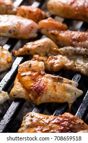 Selective focus on chicken breasts frying on the barbecue grill.