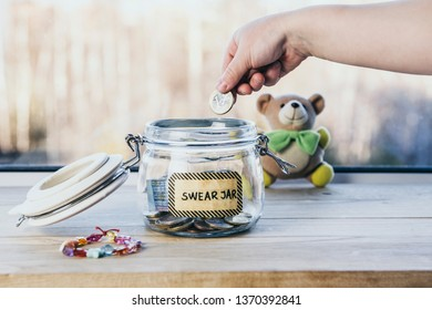 Selective focus on child hand, put euro coin in swear jar. Every time child curses or swears it has to put money as punishment in jar for safe keeps. Bad habit concept. Toy bear on the background.