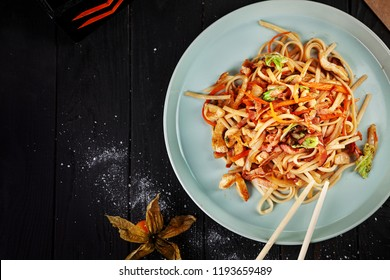 Selective focus on Chinese noodles with chicken and vegetables on dark background. Chinese cuisine, top view food, copy space for text, dark background. Asian fastfood.