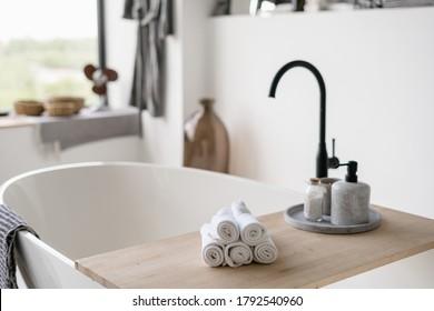 Selektiver Fokus auf saubere gefaltete Handtücher im Holzregal auf leerer und zeitgenössischer Badewanne mit modernem schwarzem Wasserhahn auf unscharfem Hintergrund. Die Innendekoration im hellen Zuhause mit weißer Inneneinrichtung