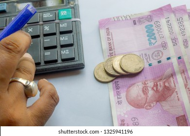 Selective Focus on Coin. Cropped hand of a woman checking account with calculator and holding a pen. Indian currency notes on table. Corporate business concept.