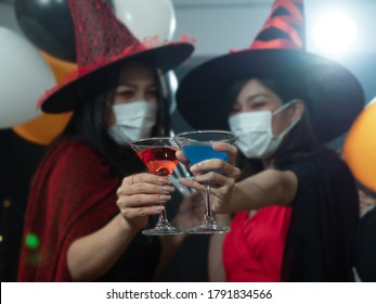 Selective focus on colorful cocktail glasses of two Asian women in Halloween costume wearing mask during pandemic outbreak of Coronavirus or Covid-19. New Normal lifestyle, Halloween party con