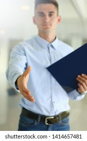 Selective focus on corporate male reaching arm to do friendly gesture. Smart and classy boy in blue shirt trying to shake hands with someone. Biz meeting concept. Office interior
