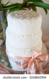 Selective focus on detail of layered decorated white wedding cake