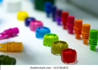 Selective focus on different type of plastic bottle cap of food and drink product. Green, yellow, red, pink, orange, blue, and purple cap closure on white table. Modern design plastic bottle cap.
