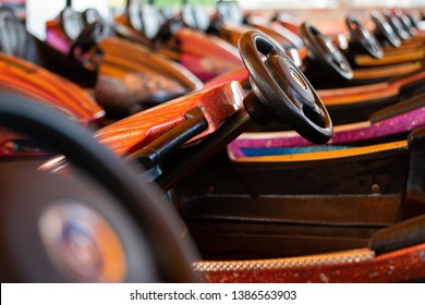Selective focus on dodgem car steering wheels in a line. Multicoloured glitter paint with black vinyl steering wheels. Bokeh background with one wheel in focus. wheels from bottom left to top right