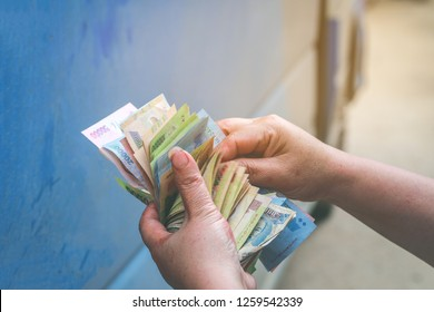 Selective focus on dong banknote on Vietnamese woman's hands