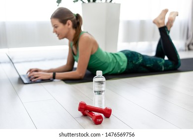 Selective focus on dumbbells and bottle of water against blurred sporty and young adult woman lying on floor at fitness mat and using laptop computer