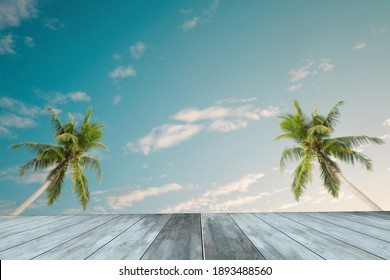 Selective focus on empty wooden table and blurred  blue sky background before sunset with two coconut trees. Free copy space for branding and use as product display montage.