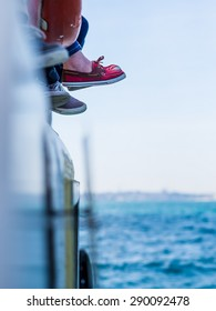 selective focus on feet hanging from the top of a boat