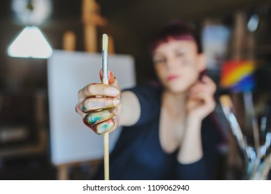 Selective focus on female artist dirty hands with different paints on them that Holding paint brushes in art studio.