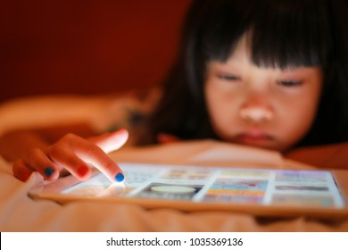 Selective focus on finger tip hand of kid, painted nails, using digital tablet while lying on white blanket in bedroom, in the dark background little girl face looking and touching at bright screen.