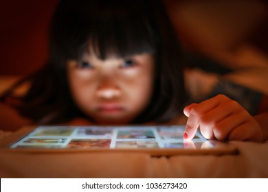 Selective focus on finger tip hand of child using online tablet while lying on the bed, in dim light background the asian teenage girl touching at bright screen and gazing eyes with insecure emotion.