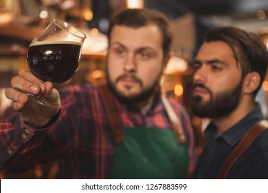 Selective focus on a glass of dark delicious beer in the hands of professional brewers. Two beermakers examining freshly brewed beer, working at their microbrewery, copy space. Business concept