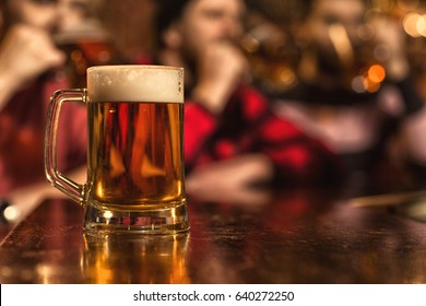 Selective focus on a glass full of beer on the counter at the bar copyspace people having fun drinking and talking on the background pub recreation relaxing weekend mood party celebrating festive