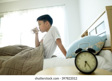 Selective focus on the glass of water drinking by young asian boy on the bed.