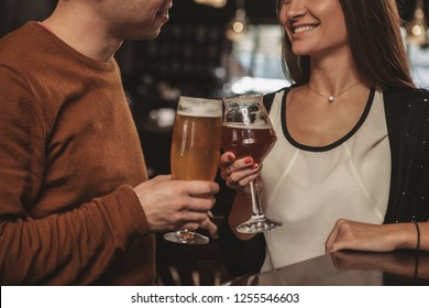 Selective focus on glasses of beer clinking in the hands of couple celebrating anniversary at restaurant. Cropped shot of a loving couple toasting with their beer glasses. Recreation, couples concept